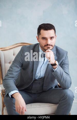 Porträt eines schönen erwachsenen Mannes in einem grauen Anzug sitzt auf einem Stuhl im Studio. Der Bräutigam wartet - Stockfoto