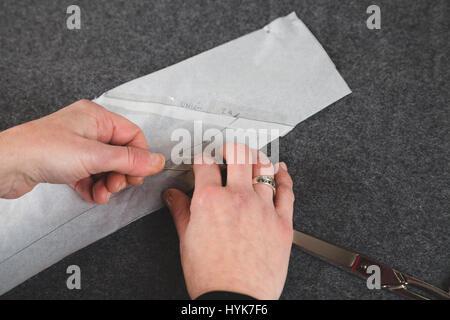 Händen der Näherin Befestigung Papierschablone mit Pins auf grauem Stoff - Stockfoto
