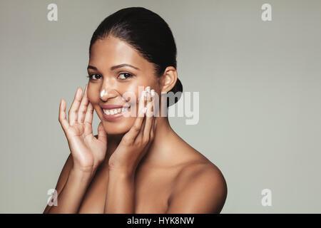 Porträt der hübsche junge Frau Auftragen der Creme auf ihr Gesicht hautnah. Lächelnd weibliches Modell mit gesunder - Stockfoto