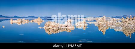 Panoramablick auf faszinierenden Tuffstein Felsformationen auf ruhige Wasseroberfläche des berühmten Mono Lake gespiegelt - Stockfoto