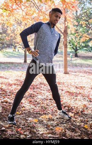 Ein junger schwarzer Mann erstreckt sich um einen Lauf vorzubereiten. Schuss in Brooklyn, New York City im Herbst - Stockfoto