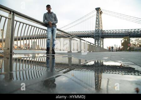 Ein junger Mann wartet entlang der East River, darunter die Williamsburg Bridge. Während des Sonnenuntergangs ein - Stockfoto