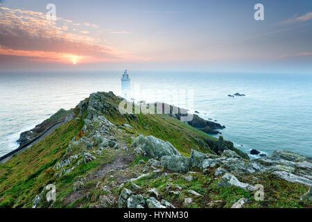 Sonnenaufgang über den Leuchtturm am Startpunkt an der Küste von Devon - Stockfoto