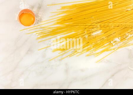 Ein Ei und Spaghetti Nudeln mit Spuren von Mehl, geschossen von oben auf eine weiße Marmor Textur mit einem Platz - Stockfoto