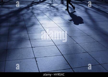 Allein eine junge Frau geht über einen New York City Park im Schatten der blauen Nacht - Stockfoto
