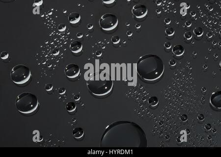 Rund geformte Wassertropfen auf der Glasoberfläche. Dunklen Hintergrund. - Stockfoto