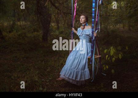 Fabelhafte Retro-Frau in einem smart Kleid im Wald sitzt auf einer Schaukel. - Stockfoto