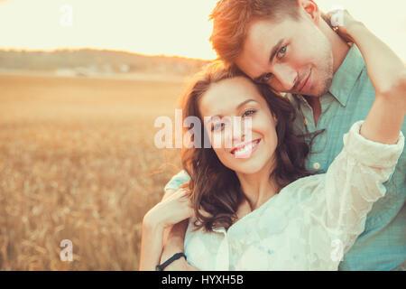 Junges Paar in Liebe outdoor. d. Paar umarmte. Junge schöne Paar in der Liebe bleiben und Küssen auf dem Feld auf - Stockfoto