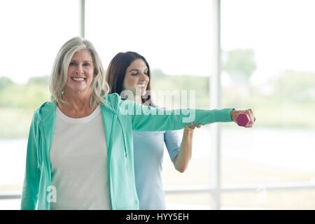 Ältere Frau mit Hand Gewicht mit personal Trainer. - Stockfoto