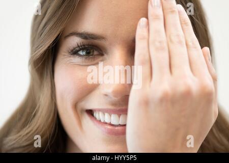 Mitte Erwachsene Frau über Auge mit der Hand. - Stockfoto