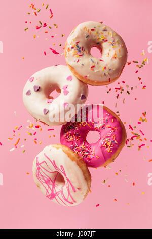 Verschiedenen dekoriert Krapfen in Bewegung fallen auf rosa Hintergrund. Süße und bunte Donuts fallen oder fliegen - Stockfoto