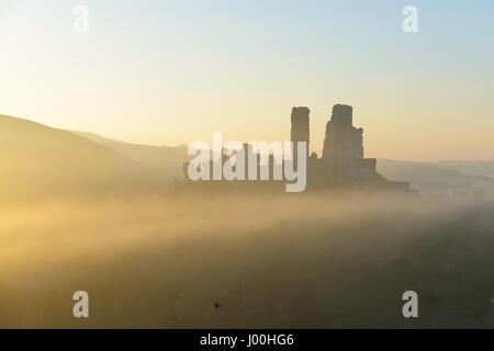 Corfe Castle, Dorset, UK. 8. April 2017. Glorreiche nebligen knackig Sonnenaufgang über die Isle of Purbeck und - Stockfoto
