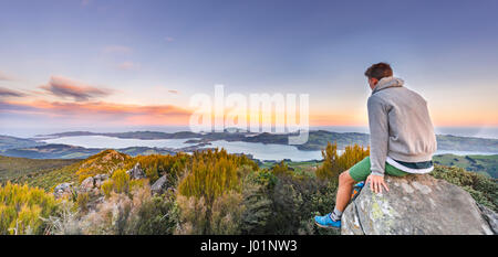 Mann, sitzen auf den Felsen, Blick vom Mount Cargill Dunedin mit Otago Hafen und Otago Peninsula, Sonnenuntergang, - Stockfoto