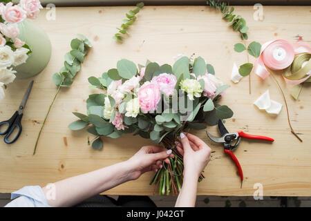 Blumengeschäft am Arbeitsplatz: hübsche junge Frau, die Mode moderne Blumenstrauß aus verschiedenen Blumen