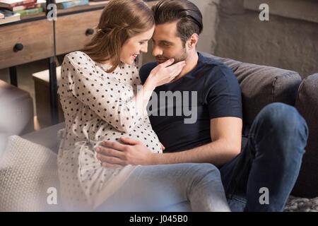 Lächelnder Mann und schwangere Frau auf dem Sofa sitzen und Stirnen berühren - Stockfoto