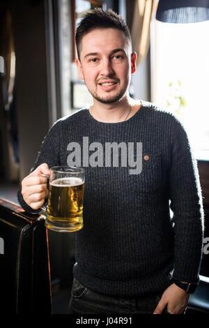 Mann in einer Kneipe oder bar hält Becher hoch in die Luft für Cheers Bier im pub - Stockfoto