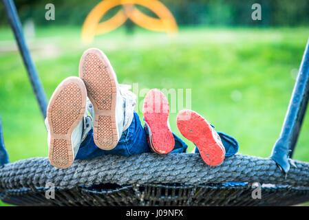 Tag-Ansicht Mutter und Kind Füße auf Schaukeln.