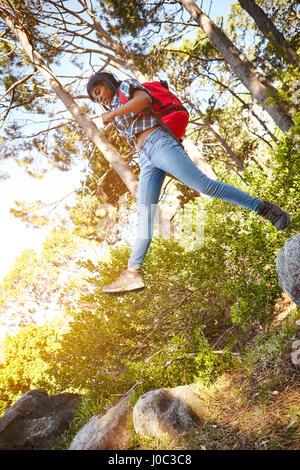 Junge Frau, Wandern, springen von einem Felsen zum anderen, Cape Town, Südafrika - Stockfoto