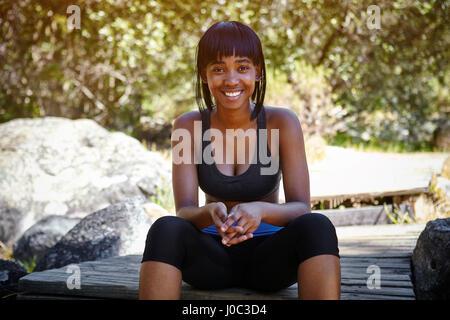 be432b41034a43 ... Porträt der jungen Frau, die im Freien sitzen, tragen Sportkleidung -  Stockfoto