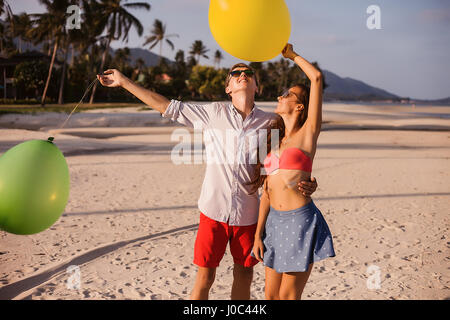 Junges Paar am Strand blickte zu Ballons, Koh Samui, Thailand - Stockfoto