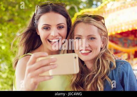Frauen, die Selfie, Karussell im Hintergrund, London, UK - Stockfoto