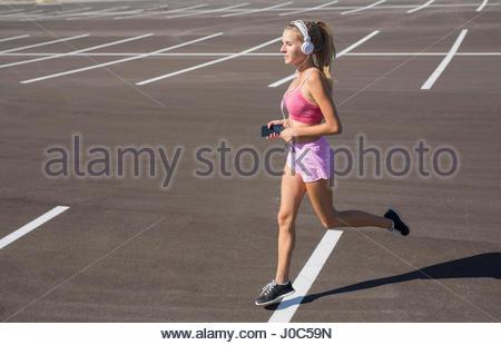Junge weibliche Läufer läuft in der Stadt Parkplatz - Stockfoto