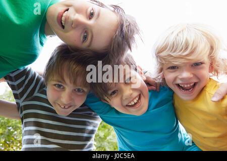 Niedrigen Winkel Ansicht von vier jungen mit Arme umeinander im park - Stockfoto