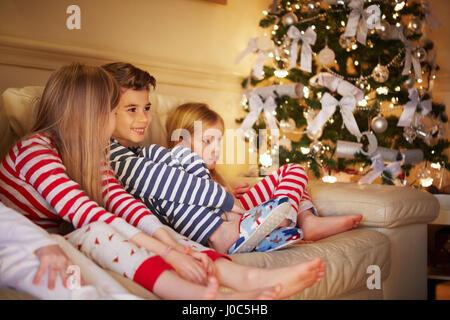 Jungen und Mädchen im gestreiften Pyjama auf Sofa zu Weihnachten - Stockfoto