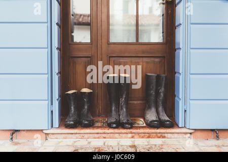 Drei Paare von Gummistiefeln vor Haustür - Stockfoto
