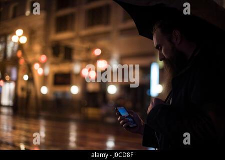 Mitte erwachsenen Mann zu Fuß in Stadt in der Nacht, mit Regenschirm, Blick auf Smartphone, Downtown, San Francisco, - Stockfoto