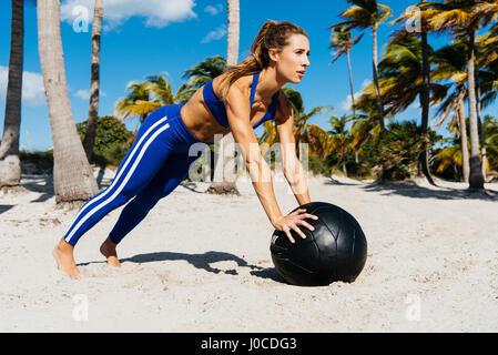 Junge Frau Ausbildung, tun Push Ups auf Gymnastikball am Strand - Stockfoto