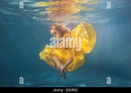 Frau im gelben Kleid Unterwasser zeigt Tanzfiguren. - Stockfoto