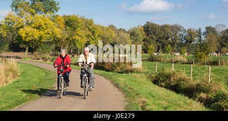 Ältere Mann und Frau mit Fahrrädern auf einem niederländischen countryroad - Stockfoto