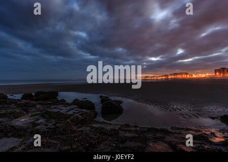 Spektakuläre bewölkten Morgen am Strand von Ostende (Belgien). Wellenbrecher Steinen im Vordergrund, Sonne über die Skyline in der Hinterg steigen ab