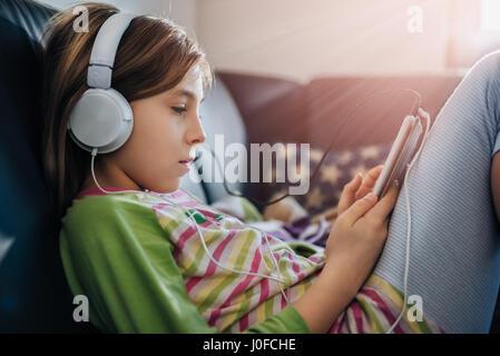 Mädchen sitzen auf schwarzes Sofa mit Tablet und Musik hören - Stockfoto