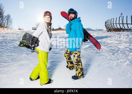 Junger Mann und Frau mit Snowboards auf dem Hügel stehen und Lächeln - Stockfoto