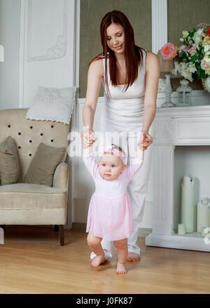 junge Mutter lehrt ihr Baby zu Hause gehen - Stockfoto