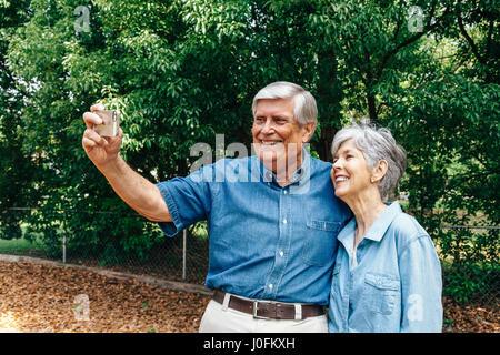 Älteres paar nehmen Selfie im Park - Stockfoto