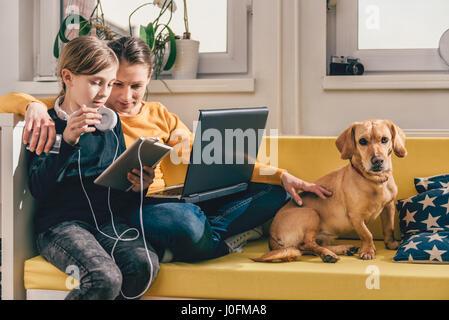 Mutter und Tochter sitzen auf gelben Sofa mit kleinen gelben Hund und die Verwendung von Tablet-PC und Laptop - Stockfoto