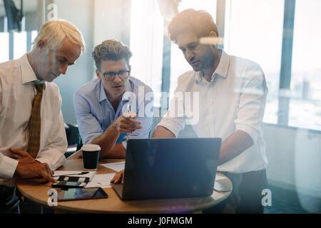 Geschäftsleuten stehen vom Tisch im Büro sprechen. Unternehmer geben, demonstrieren auf Laptop an Kollegen - Stockfoto