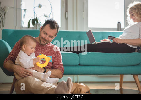 Vater auf dem Boden sitzend und hält Baby im Arm während Frau auf Sofa sitzen und tun, Online-shopping mit Kreditkarte - Stockfoto