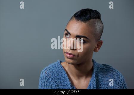 Transgender-Frau stehend vor grauem Hintergrund wegschauen - Stockfoto