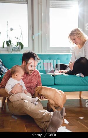 Vater sitzt auf dem Boden und mit Baby im Arm spielen mit Hund während Frau auf Sofa sitzen und tun, Online-shopping - Stockfoto