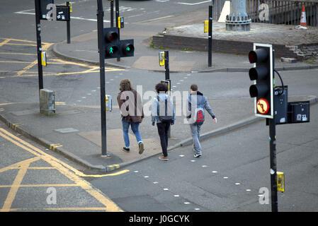 drei 3 jungen im Teenageralter Studenten Straße am grünen Mann auf Ampel überqueren - Stockfoto