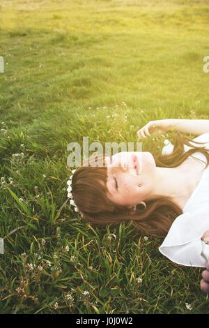 Jungen Hippie-Frau schläft auf der grünen Wiese - Stockfoto