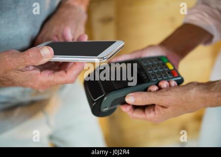 Kunde die Zahlung durch NFC-Technologie auf dem Handy in Cafà© - Stockfoto