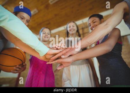 High-School-Kids mit ihren Händen gestapelt in Basketballplatz - Stockfoto