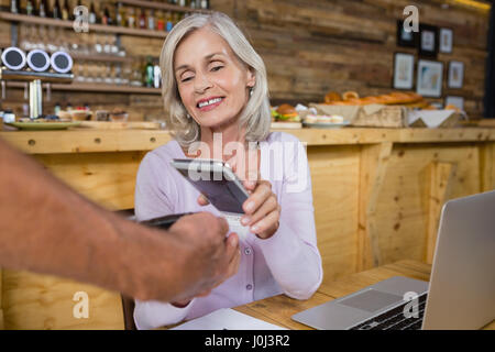 Ältere Frau die Zahlung durch NFC-Technologie auf dem Handy in Cafà© - Stockfoto