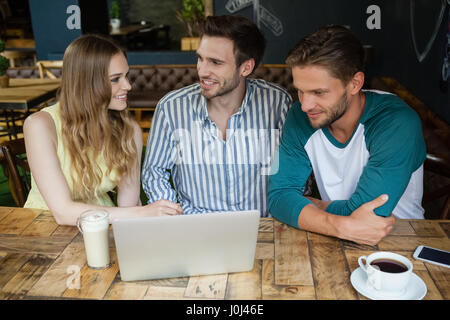 Glückliche Freunde betrachten digitaler Laptop sitzend vom Tisch im Café shop - Stockfoto