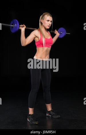 Seitenansicht der sportliche Frau, die das Training mit der Langhantel auf schwarz - Stockfoto